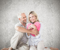 Composite image of happy couple sitting and holding heart pillow Royalty Free Stock Images