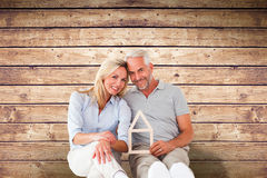 Composite image of happy couple sitting and holding house outline Royalty Free Stock Photos