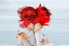Composite image of happy couple sitting and holding paintbrushes Stock Image