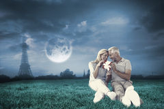Composite image of happy couple sitting and holding present Stock Image