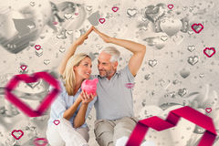Composite image of happy couple sitting and sheltering piggy bank. Happy couple sitting and sheltering piggy bank against grey valentines heart pattern Stock Images
