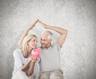Composite image of happy couple sitting and sheltering piggy bank. Happy couple sitting and sheltering piggy bank against weathered surface Stock Photos