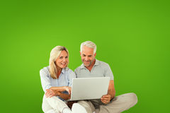 Composite image of happy couple sitting and using laptop Royalty Free Stock Photography