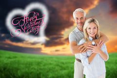 Composite image of happy couple smiling at camera and embracing Royalty Free Stock Photography