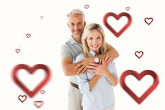 Composite image of happy couple smiling at camera and embracing. Happy couple smiling at camera and embracing against hearts stock image