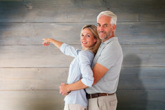 Composite image of happy couple smiling at camera and pointing Stock Photos