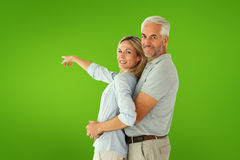 Composite image of happy couple smiling at camera and pointing Royalty Free Stock Photography