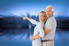 Composite image of happy couple smiling at camera and pointing Royalty Free Stock Photo