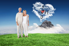 Composite image of happy couple smiling at camera together. Happy couple smiling at camera together against cloud heart Royalty Free Stock Images