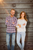 Composite image of happy couple standing with arms crossed Stock Photography