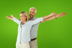 Composite image of happy couple standing with arms outstretched Stock Photo