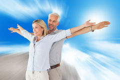 Composite image of happy couple standing with arms outstretched Royalty Free Stock Photography