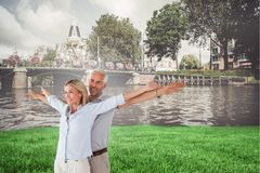 Composite image of happy couple standing with arms outstretched Stock Images