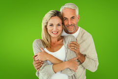 Composite image of happy couple standing and hugging. Happy couple standing and hugging against green vignette Stock Photos