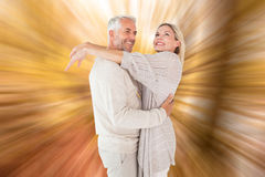 Composite image of happy couple standing and hugging Stock Image