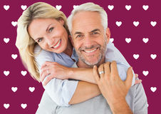 Composite image of happy couple standing and hugging. Happy couple standing and hugging against valentines day pattern royalty free stock images