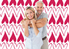 Composite image of happy couple standing and hugging. Happy couple standing and hugging against valentines day pattern stock photo
