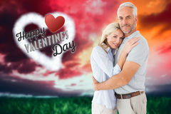 Composite image of happy couple standing and smiling at camera Stock Images