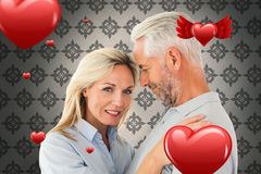 Composite image of happy couple standing and smiling at camera. Happy couple standing and smiling at camera against grey wallpaper royalty free stock photo