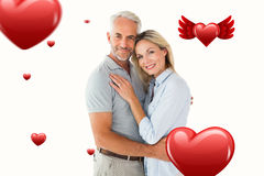 Composite image of happy couple standing and smiling at camera. Happy couple standing and smiling at camera against hearts stock photos