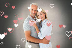 Composite image of happy couple standing and smiling at camera. Happy couple standing and smiling at camera against white background with vignette stock images