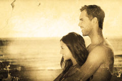 Composite image of happy couple in swimsuit hugging while looking at the water Royalty Free Stock Images