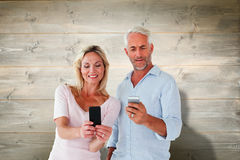 Composite image of happy couple texting on their smartphones. Happy couple texting on their smartphones against bleached wooden planks background Royalty Free Stock Photo