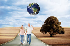 Composite image of happy couple walking holding hands Royalty Free Stock Photo