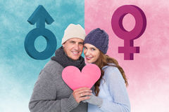 Composite image of happy couple in warm clothing holding heart Stock Image