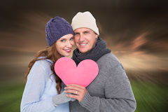 Composite image of happy couple in warm clothing holding heart Royalty Free Stock Images