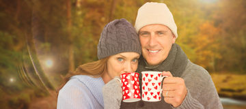 Composite image of happy couple in warm clothing holding mugs Royalty Free Stock Photography