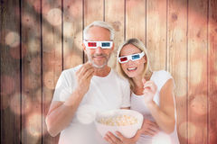 Composite image of happy couple wearing 3d glasses eating popcorn Royalty Free Stock Image