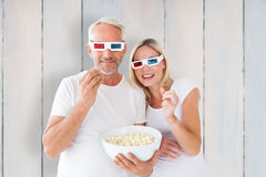 Composite image of happy couple wearing 3d glasses eating popcorn Stock Photos