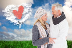 Composite image of happy couple in winter fashion embracing Stock Images