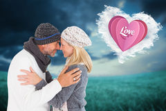 Composite image of happy couple in winter fashion embracing Royalty Free Stock Images