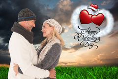 Composite image of happy couple in winter fashion embracing Stock Photos