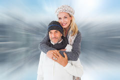 Composite image of happy couple in winter fashion embracing Stock Photography