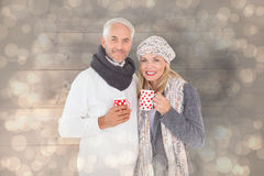 Composite image of happy couple in winter fashion holding mugs Royalty Free Stock Photography