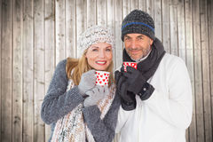 Composite image of happy couple in winter fashion holding mugs. Happy couple in winter fashion holding mugs against wooden planks background royalty free stock images