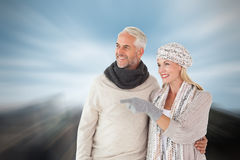 Composite image of happy couple in winter fashion looking Stock Images