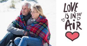 Composite image of happy couple wrapped up in blanket sitting on the beach. Happy couple wrapped up in blanket sitting on the beach against love is in the air Stock Photography