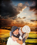 Composite image of happy cute couple romancing while embracing each other. Happy cute couple romancing while embracing each other against country scene Stock Photography