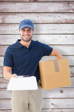 Composite image of happy delivery man with cardboard box and clipboard Royalty Free Stock Images