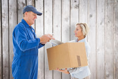 Composite image of happy delivery man with customer Stock Photos