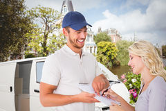 Composite image of happy delivery man getting signature from customer Stock Image