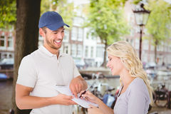 Composite image of happy delivery man getting signature from customer. Happy delivery men getting signature from customer against canal in amsterdam Royalty Free Stock Images