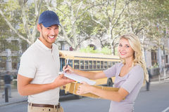 Composite image of happy delivery man giving package to customer Stock Photo