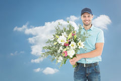 Composite image of happy delivery man holding bouquet Stock Images