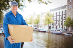 Composite image of happy delivery man holding cardboard box Royalty Free Stock Image