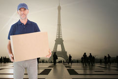 Composite image of happy delivery man holding cardboard box Stock Photography